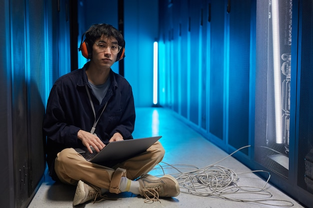 Portrait complet d'un jeune homme asiatique assis sur le sol dans la salle des serveurs éclairée par la lumière bleue lors de la configuration du réseau de superordinateurs, espace de copie