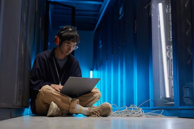 Portrait complet d'un jeune homme asiatique assis sur le sol dans la salle des serveurs éclairée par la lumière bleue lors de la configuration du réseau de superordinateurs via un ordinateur portable, espace de copie