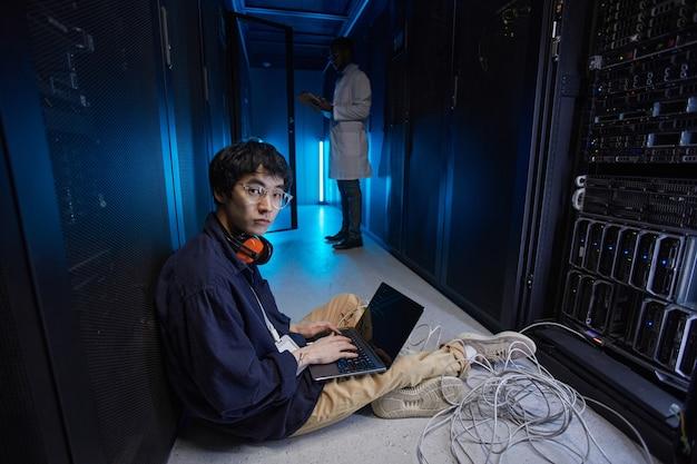Portrait complet d'un jeune homme asiatique assis sur le sol dans la salle des serveurs lors de la configuration du réseau de superordinateurs, espace de copie