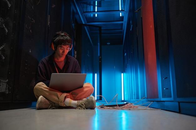 Portrait complet d'un jeune homme asiatique utilisant un ordinateur portable alors qu'il était assis sur le sol dans la salle des serveurs éclairée par la lumière bleue et installant un réseau de superordinateurs, espace de copie