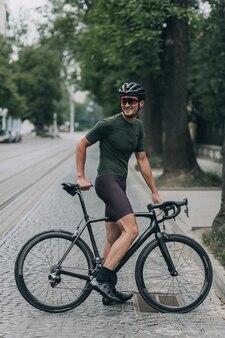 Portrait complet d'un jeune homme en vêtements de sport, casque et lunettes regardant de côté tout en se reposant sur le vélo après un entraînement en plein air. concept de personnes, passe-temps actif et loisirs.