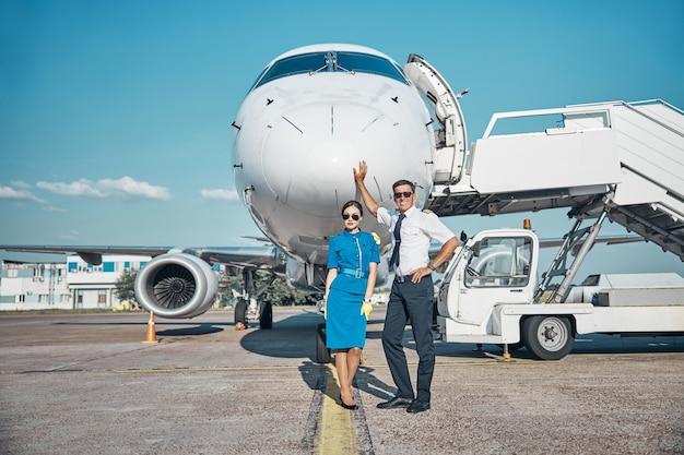 Portrait complet d'un jeune pilote joyeux et d'une hôtesse de l'air en lunettes de soleil debout sur la piste après l'arrivée