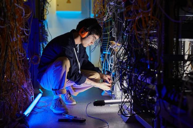 Portrait complet d'un jeune technicien réseau connectant des câbles et des fils lors de la configuration de la connexion internet dans la salle des serveurs, espace de copie