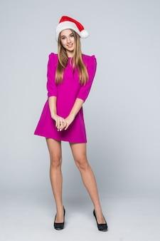Portrait complet de jolie belle fille aux cheveux d'or en robe rose et chapeau de nouvel an isolé sur blanc