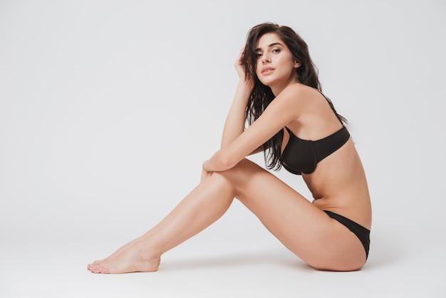 Portrait complet d'une jolie femme séduisante en lingerie assise sur le sol et regardant à l'avant sur une surface blanche
