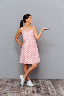 Portrait complet d'une jolie fille joyeuse tenant un fond sur la paume sur un mur gris
