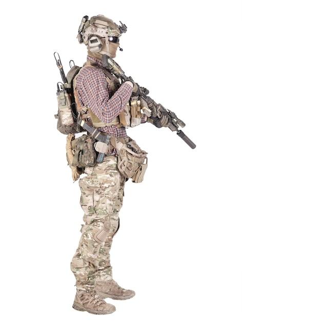 Portrait complet d'un joueur d'airsoft en chemise à carreaux, vêtu d'un uniforme de camouflage, casque avec casque radio tactique, gilet pare-balles, visant avec une réplique de fusil de service shoot isolé sur blanc