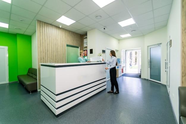 Portrait complet d'une patiente conversant avec une infirmière à la réception de l'hôpital.