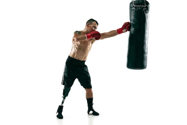 Portrait complet d'un sportif musclé avec jambe prothétique, espace de copie. boxer masculin en gants rouges s'entraînant et s'exerçant. isolé sur mur blanc. concept de sport, mode de vie sain.