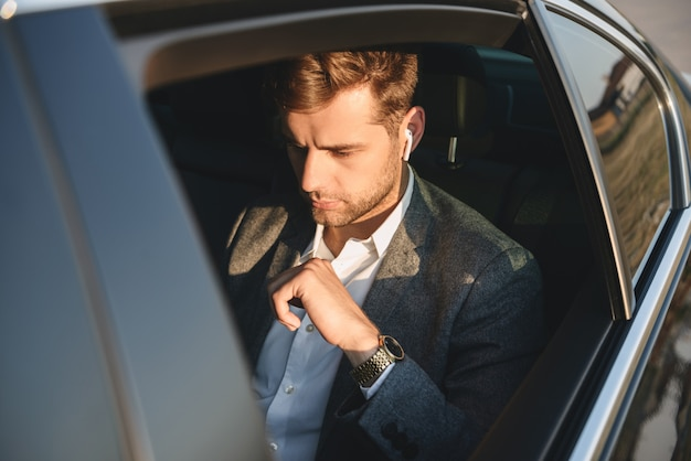Portrait, de, concentré, caucasien, homme, porter, businesslike, complet, et, earpod, dos, séance, quoique, équitation, dans voiture
