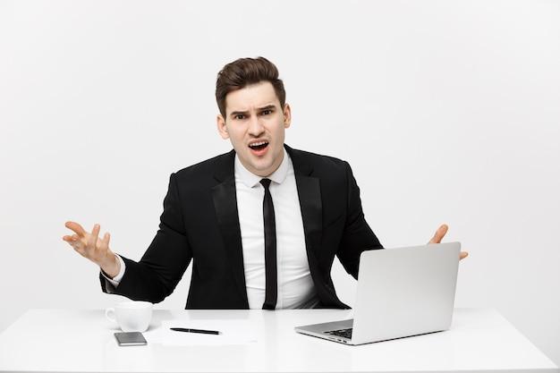 Portrait de concept d'entreprise d'un homme d'affaires en colère criant assis au bureau isolé sur fond blanc...