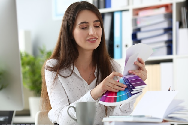Portrait de concepteur souriant en choisissant la palette de couleurs