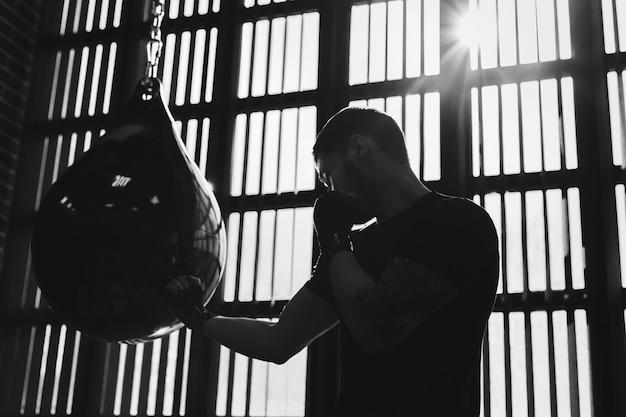 Portrait conceptuel d'un boxeur tatoué brutal qui s'entraîne sur le ring et frappe un sac de boxe. noir et blanc