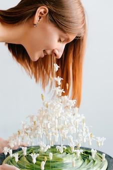 Portrait conceptuel créatif de jeune fille inhabituelle. jolie femme en robe de style grec blanc sentant la composition originale de bouquet de printemps de fleurs à l'intérieur. douceur, facilité, tendresse. bonheur, joie de vivre