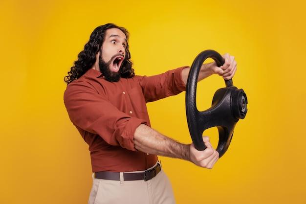 Portrait d'un conducteur imprudent choqué tenant le volant bouche ouverte sur fond jaune