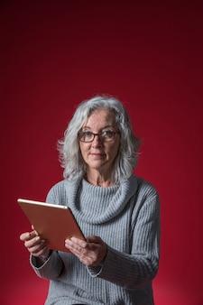 Portrait, confiance, femme aînée, tablette numérique, main, regarder, appareil photo, contre, toile de fond rouge