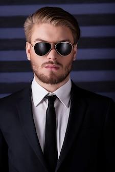 Portrait de confiance et de masculinité. portrait de beau jeune homme à lunettes de soleil et tenues de soirée regardant la caméra en se tenant debout sur fond rayé