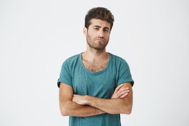 Portrait de confiant attrayant jeune mec espagnol en t-shirt bleu et coupe de cheveux élégante, croisant les mains, étant super jaloux en voyant l'ex petite amie avec un nouvel homme.