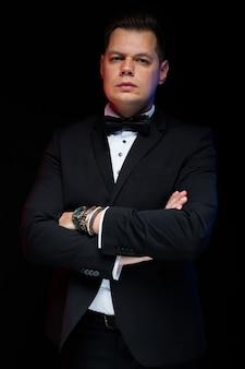Portrait de confiant beau élégant homme d'affaires élégant avec noeud papillon avec bras croisés