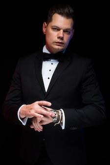 Portrait de confiant beau élégant homme d'affaires élégant avec noeud papillon avec la main sur la main en noir en studio