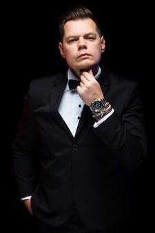 Portrait de confiant beau élégant homme d'affaires élégant avec noeud papillon tenant la main près de barbe sur fond noir en studio