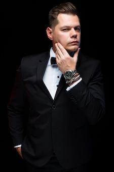 Portrait de confiant beau élégant homme d'affaires élégant avec noeud papillon, tenant la main près de barbe sur fond noir en studio