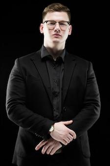 Portrait de confiant beau élégant homme d'affaires responsable dans des verres avec main sur main debout sur fond noir