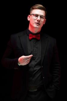 Portrait de confiant beau élégant homme d'affaires responsable avec la main sur sa veste sur fond noir