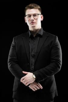 Portrait de confiant beau élégant responsable homme d'affaires dans des verres avec la main sur debout debout
