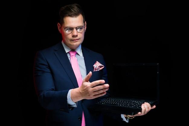 Portrait, confiant, beau, homme affaires sérieux, projection, sur, ordinateur portable, geste main, isolé, sur, noir