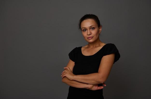 Portrait confiant d'une belle femme sereine d'origine africaine pose avec les bras croisés sur la taille, regarde la caméra isolée sur fond de mur gris avec espace de copie pour la publicité