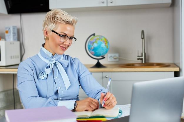 Portrait de confiant bon à l'enseignant assis à table