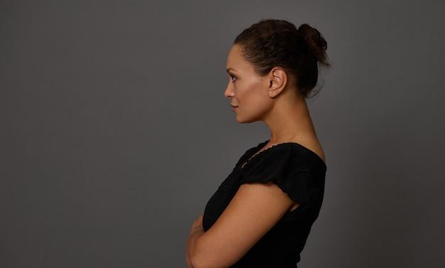 Portrait confiant d'une femme d'âge moyen vêtue de noir sur un fond de mur gris avec espace de copie pour la publicité