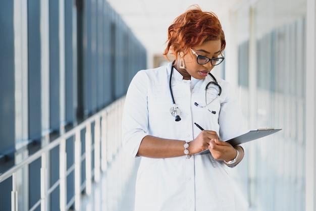 Portrait confiant femme médecin afro-américaine médecin professionnel écrit notes patient isolé sur fond de fenêtres de couloir clinique hôpital. expression positive du visage