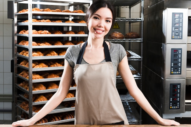 Portrait, confiant, jeune, boulanger, femme, debout, devant, étagères croissant croissant
