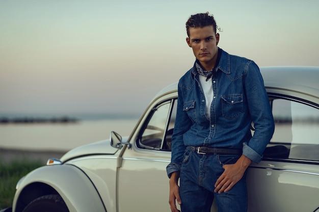 Portrait confiant jeune homme décontracté avec une vieille voiture à la plage. image filtrée.