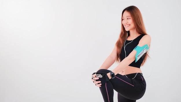 Portrait de confiante belle femme fitness asiatique écouter de la musique et se réchauffer avant l'exercice