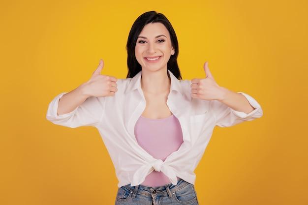 Portrait de conseiller fille positive lever deux pouces sur fond jaune