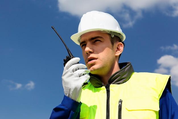 Portrait de constructeur avec émetteur dans le ciel bleu