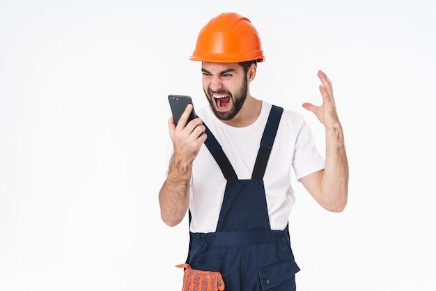 Portrait d'un constructeur de jeune homme criant en colère négative en casque posant isolé sur un mur blanc à l'aide d'un téléphone portable.