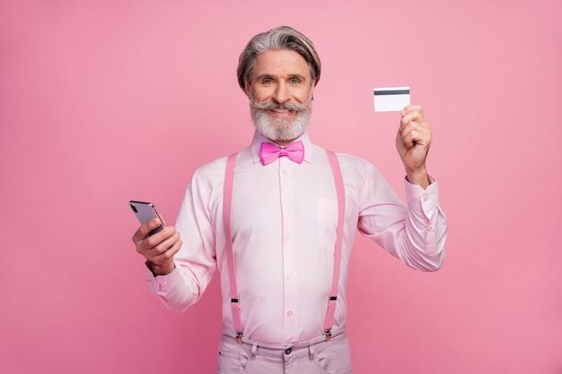 Portrait de contenu heureux homme tenant en mains la carte de débit