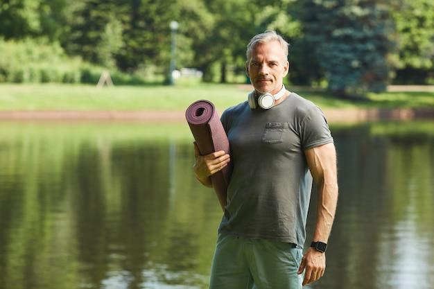Portrait de contenu homme mûr musclé avec des écouteurs autour du cou tenant un tapis d'exercice contre le lac du parc