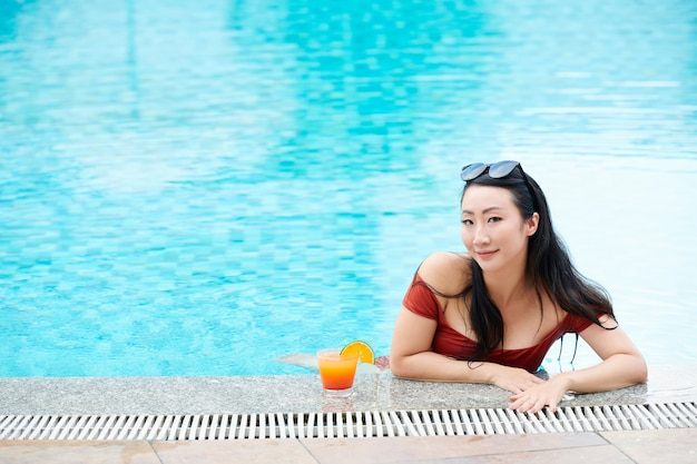 Portrait de contenu jeune femme asiatique avec des lunettes de soleil sur la tête appuyée au bord de la piscine