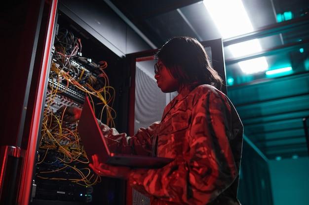 Portrait en contre-plongée d'une femme afro-américaine gérant un réseau informatique tout en travaillant avec un superordinateur dans la salle des serveurs éclairée par la lumière rouge, espace de copie