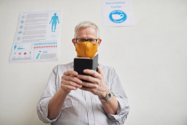 Portrait en contre-plongée d'un homme âgé aux cheveux blancs utilisant un smartphone en faisant la queue à la clinique médicale, espace pour copie