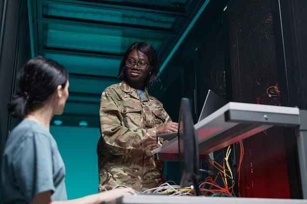 Portrait en contre-plongée d'une jeune femme afro-américaine portant un uniforme militaire à l'aide d'un ordinateur lors de la configuration du réseau dans la salle des serveurs