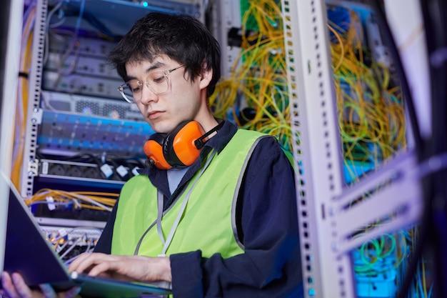 Portrait en contre-plongée d'un jeune technicien réseau utilisant un ordinateur portable dans la salle des serveurs lors de la configuration de la connexion internet, espace de copie
