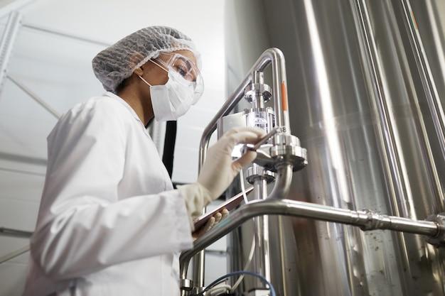 Portrait en contre-plongée d'une jeune travailleuse portant des vêtements de protection lors de l'utilisation d'équipements dans une usine chimique, espace pour copie