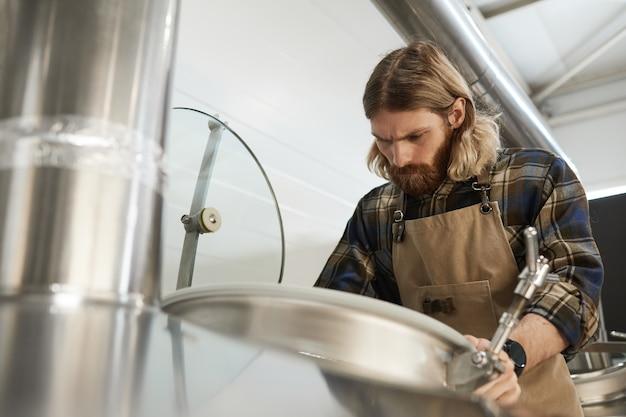 Portrait en contre-plongée d'un maître brasseur barbu contrôlant la production à l'usine de fabrication de bière, espace de copie