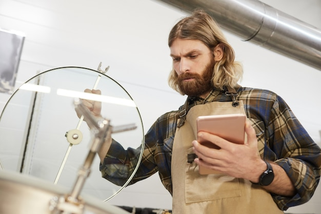 Portrait en contre-plongée d'un maître brasseur barbu inspectant la production à l'usine de fabrication de bière, espace de copie